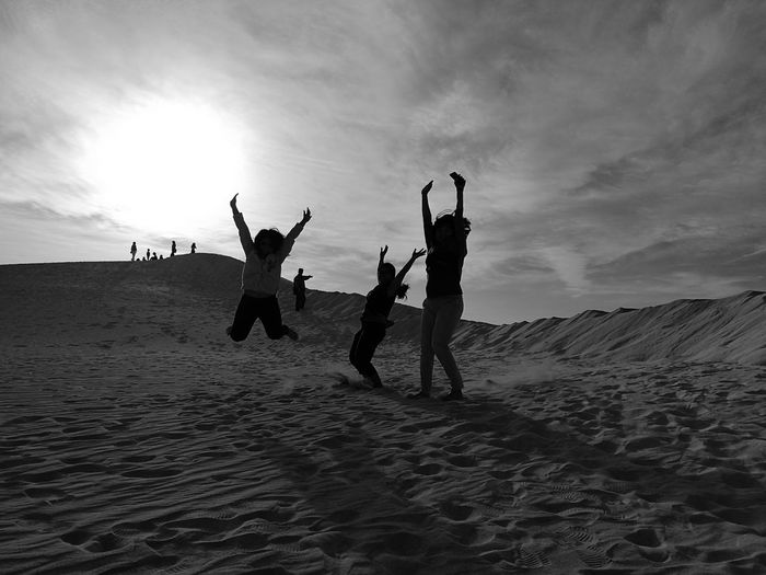 People enjoying at beach against sky