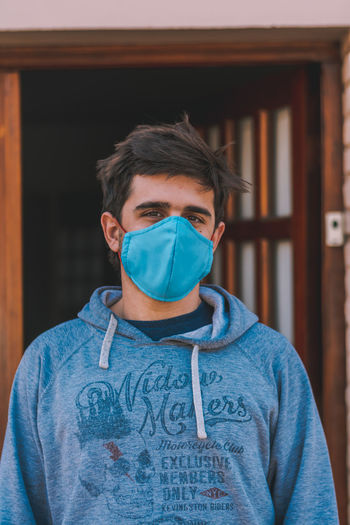 Portrait of young man wearing mask standing against house