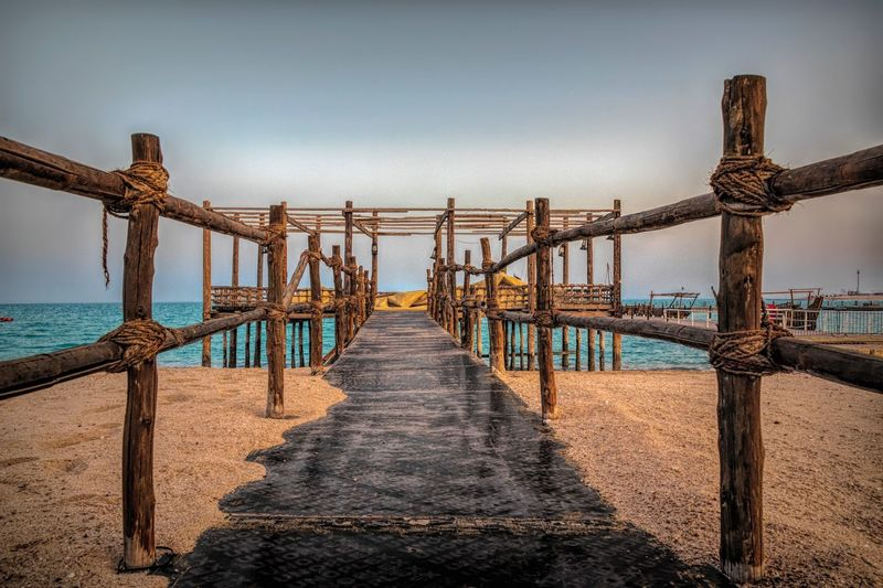 Wooden bridge Sea Water Sky Nature Built Structure Architecture Railing No People The Way Forward Horizon Over Water Diminishing Perspective Beach Direction