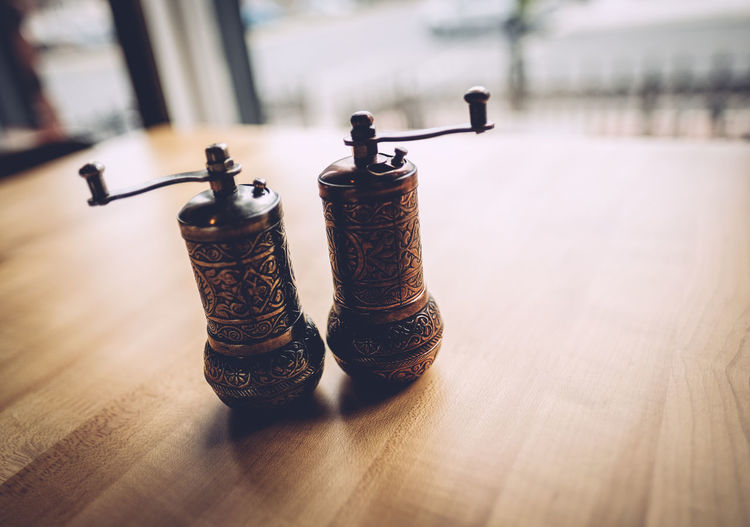 Close-up of antique salt and pepper shakers on table at restaurant