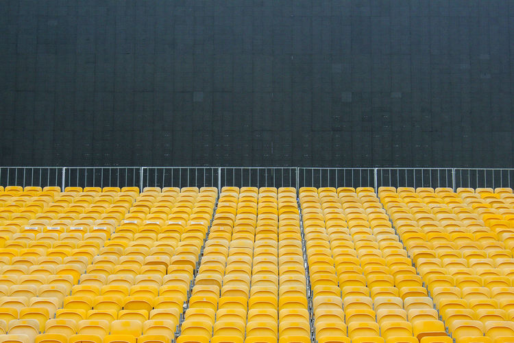 Chairs Large Group Of Objects Long No People Outdoors Row Of Things Seats Stadium Yellow Yellow Seats The Color Of Sport