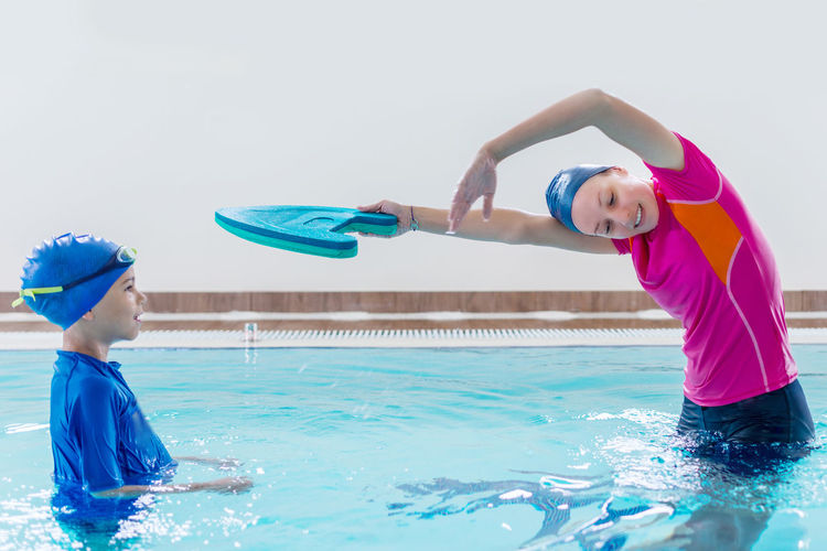 Mother teaching swimming to son in pool