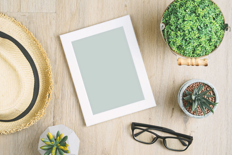 Blank photo frame placed on a wooden floor adorned with potted plants, hats and glasses. Background Beautiful Beauty Blank Border Card Closeup Composition Copy Cozy Cute Decor Decoration Design Desk Empty Flat Floor Frame Glasses Green Hat Hipster House Image Interior Isolated Lay Leaf Life Minimal Mockup Nature New Paper Photo Photography Picture Plant Pot Rustic Space Table Texture Top View Wall White Wood Wooden