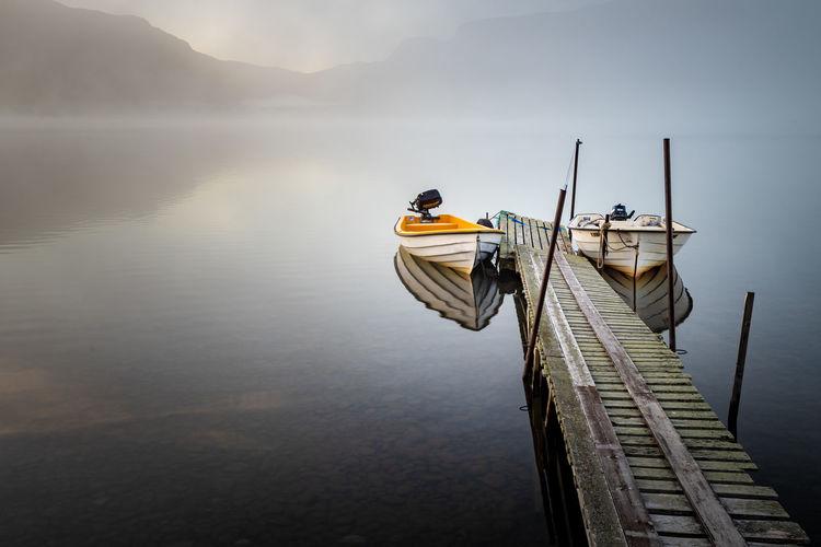 Boat moored on pier over lake against sky