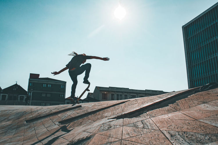 Low angle view of man jumping on built structure against sky