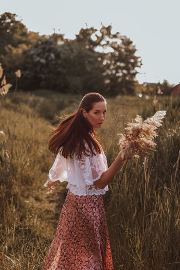 Young brunette women in a white blouse and long skirt with a bouquet of dried flowers in the field