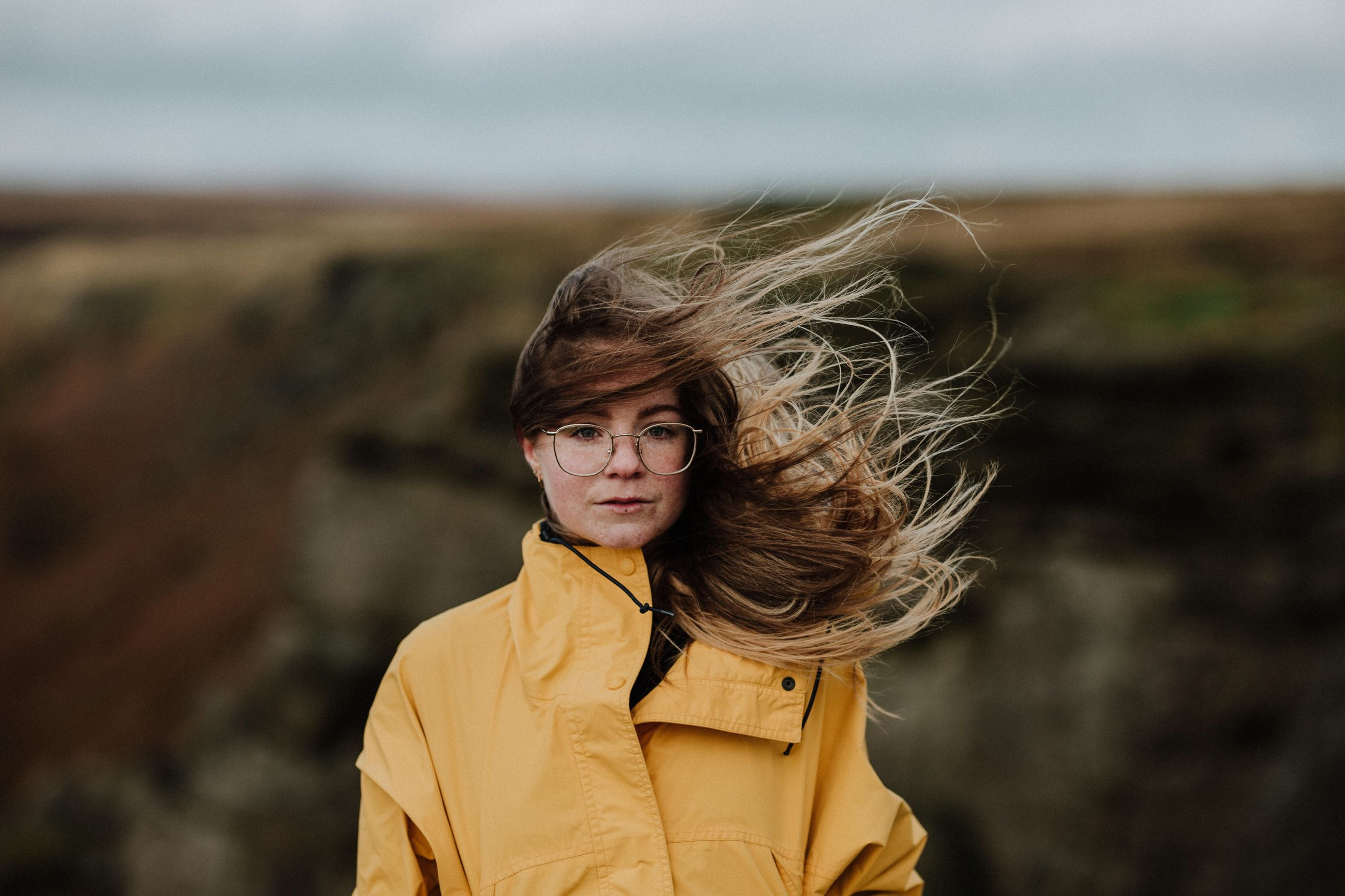 real people, focus on foreground, one person, young women, front view, casual clothing, looking at camera, leisure activity, young adult, lifestyles, standing, outdoors, day, nature, portrait, yellow, sky, beautiful woman, beauty in nature