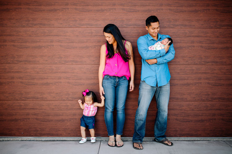 Full length of father with daughter standing against wall