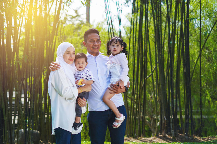 Playful family spending time together at park. Group Of People Men Standing Togetherness Child Childhood Family Males  Parent Offspring Boys Tree Three Quarter Length Son Nature Smiling Father Females Plant Mother Positive Emotion Outdoors