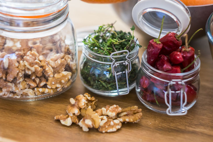 Close up of fresh healthy food ingredients like nuts and chiully pepper - piece of tqable in the kitchen - restaurant and fresh fruits and vegatables Food Food And Drink Jar Healthy Eating Container Freshness Wellbeing Table Indoors  No People Fruit Vegetable Close-up Glass - Material Focus On Foreground Ingredient Transparent Nut - Food Still Life Bowl Snack Agriculture Chilly Pepper Dinner Family Kitchen Preparing Food Wood Vitamin Vegetarian Food Spice Perfume Lifestyles