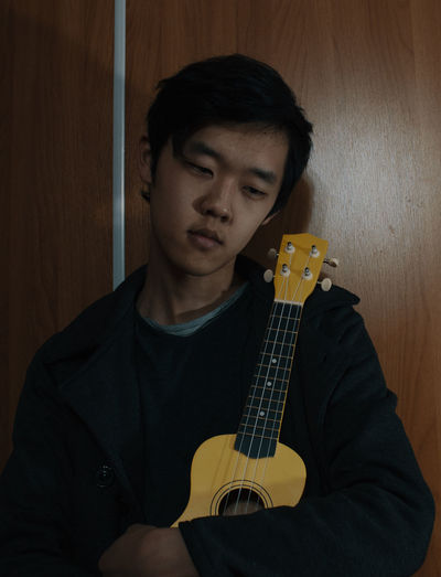 Teenage boy holding ukulele against wooden door