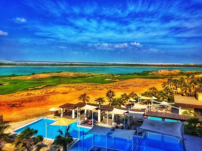 Luxury lifestyle the Abu Dhabi way..... Golf Course View Golf Course Golf Luxury Hotel Luxurylifestyle  Shot On IPhone UAE Abu Dhabi Water Sky Sea Cloud - Sky Nature Land Chair Swimming Pool Blue Scenics - Nature Day Pool No People Beauty In Nature High Angle View Horizon Over Water Architecture Beach Outdoors