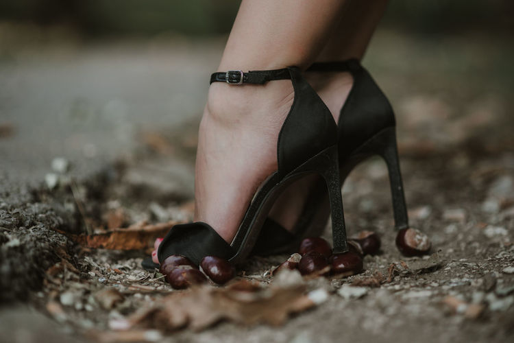 Low section of woman wearing high heels in forest