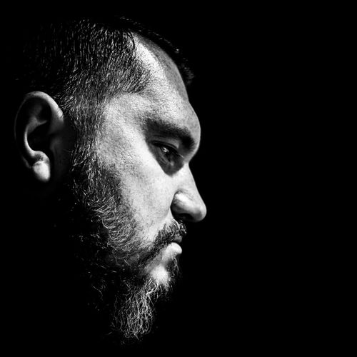 Close-Up Of Man Serious Bearded Man Against Black Background