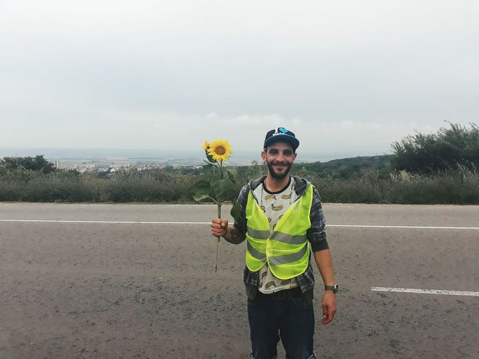 Portrait of young man holding sunflower while standing on road against sky