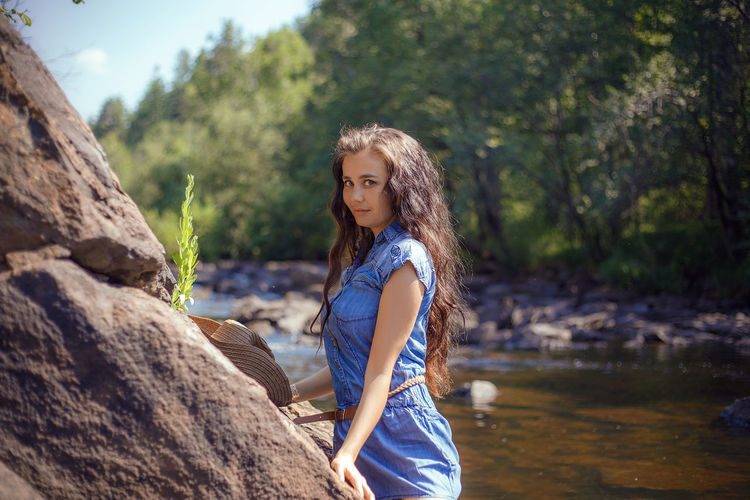 Portrait of young woman standing against stream