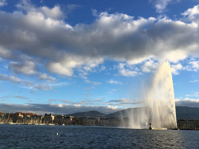 Fountain in city by sea against sky