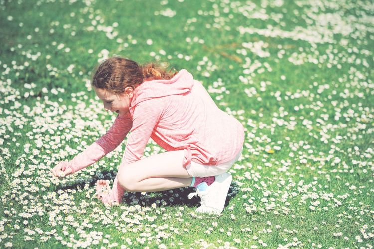 Side view of a girl sitting on grass