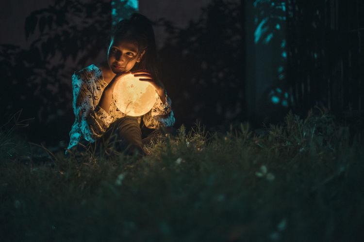 Girl holding illuminated toy sitting on field at night