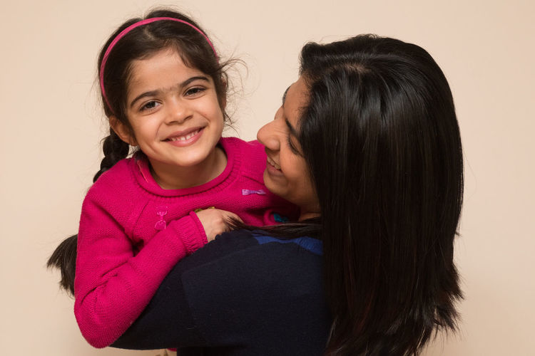 Portrait of happy mother with daughter against beige background