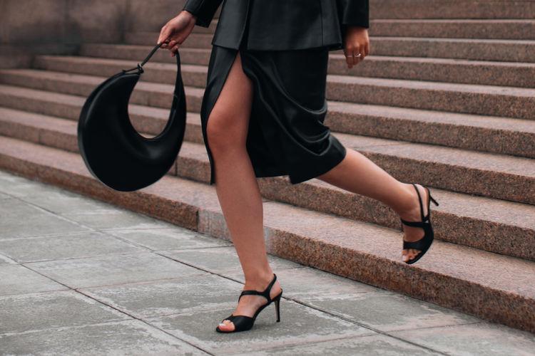 Stylish woman walking around the city in a fashionable black leather jacket, skirt, heels, handbag.