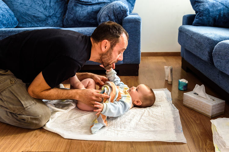 Father playing with baby at home