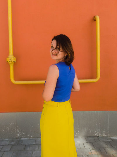 Portrait Of Woman Standing On Footpath Against Orange Wall