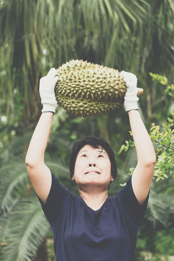 Close-up of woman holding durian against trees