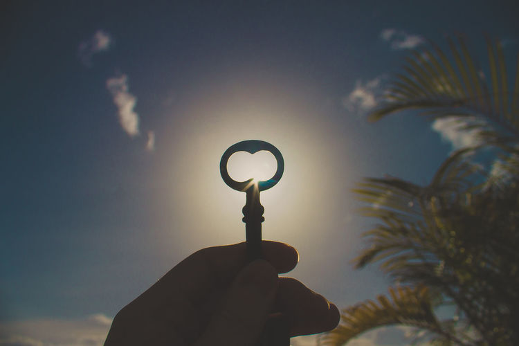 Cropped Hand Of Person Holding Key Against Sky