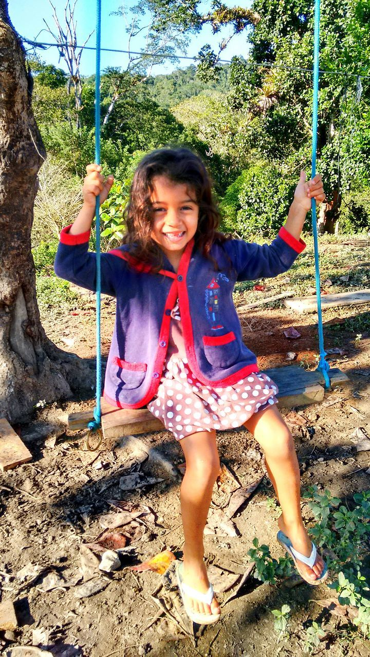smiling, childhood, happiness, swing, one person, tree, day, outdoors, full length, front view, girls, looking at camera, real people, elementary age, holding, rope swing, portrait, playing, lifestyles, cheerful, people