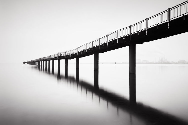 fineart black and white pier at sea Beauty In Nature Black & White Blackandwhite Calm Day Fine Art Photography Fineart_photobw Idyllic In A Row Jetty Nature No People Non-urban Scene Ocean Outdoors Pier Reflection Scenics Sky Standing Water Tranquil Scene Tranquility Water Wood - Material Wooden Post