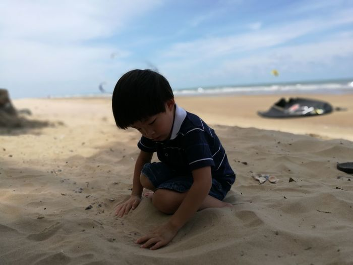 Cute boy playing with sand against sky at beach