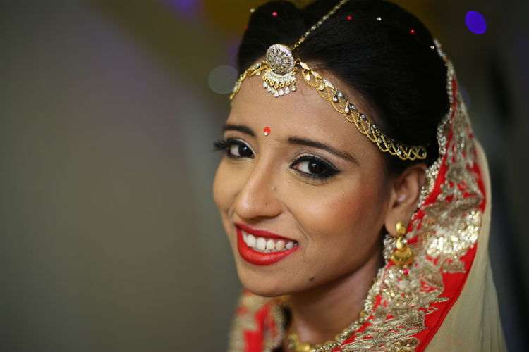 Portrait of happy bride standing against wall