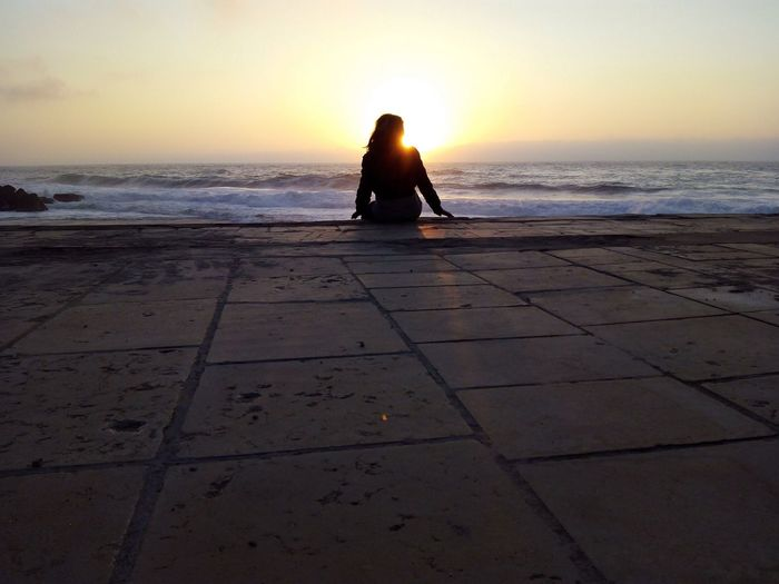 Rear View Of Woman Sitting On Tiled Floor Against Sea During Sunset