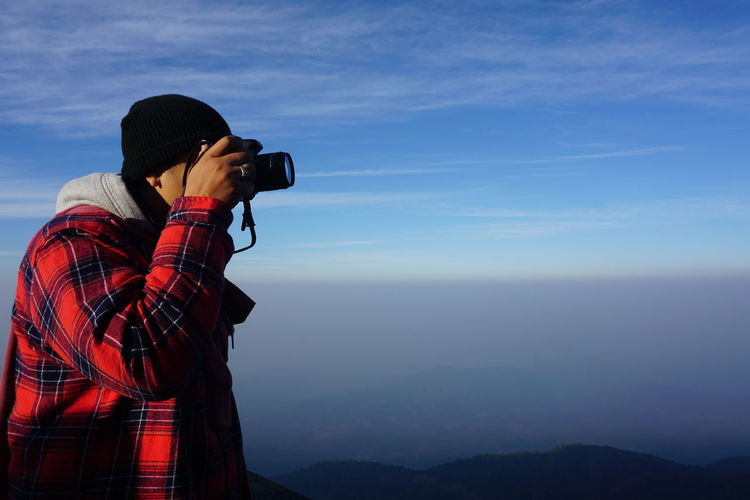 Man photographing against blue sky