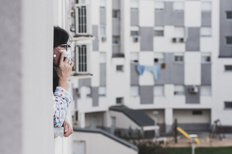 Woman wearing mask talking on phone at balcony