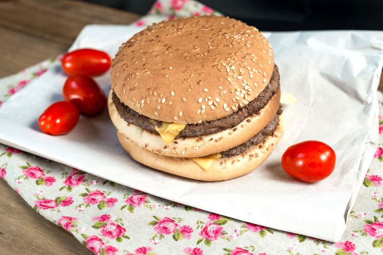 High angle view of hamburger with tomatoes on paper over table