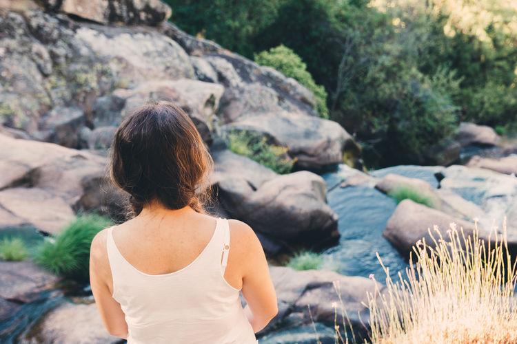 Rear view of woman looking at rocks