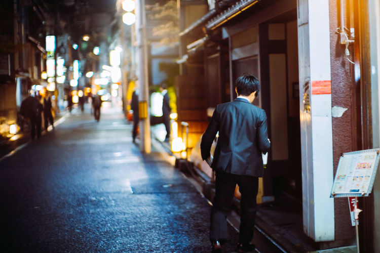 Rear view of man walking on street amidst buildings at night