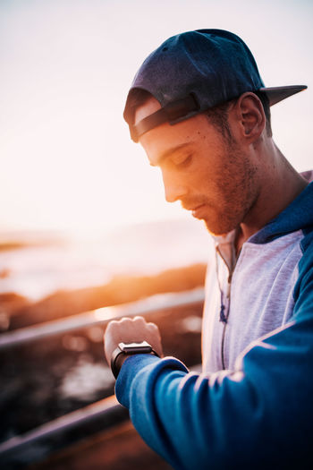 Close-up of man looking at smartwatch at sunset