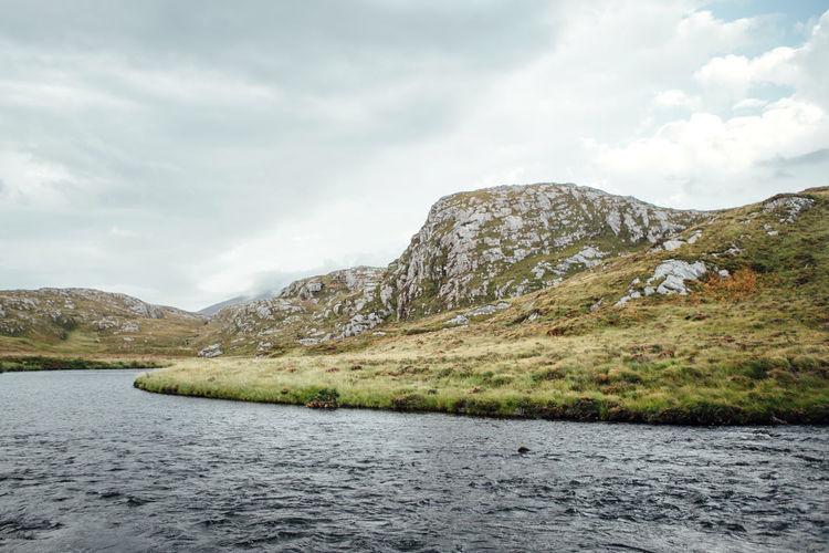 Calm countryside lake against mountain range