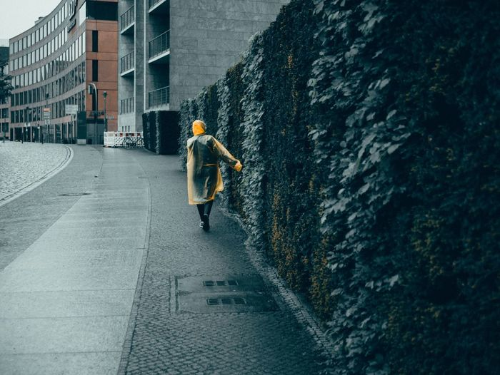 Rear view of woman in raincoat walking at sidewalk