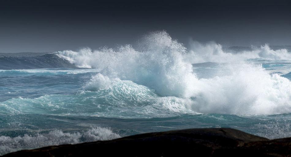 Sea waves splashing on shore against sky