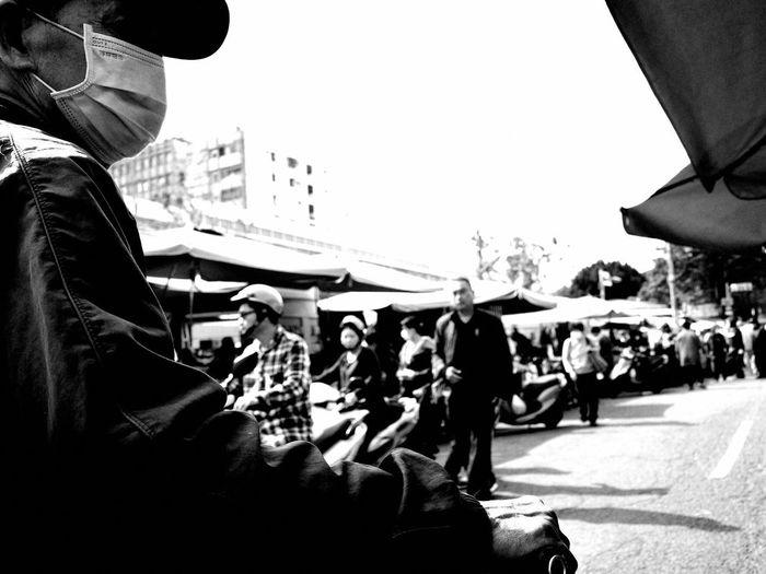 People on city street against sky