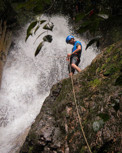 Low angle view of man tying rope while standing on cliff against waterfall