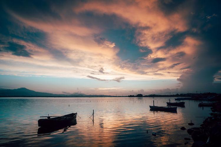 Pink colored sunset at santa gilla with fisherman harbor and boats, cagliari, sardinia, italy