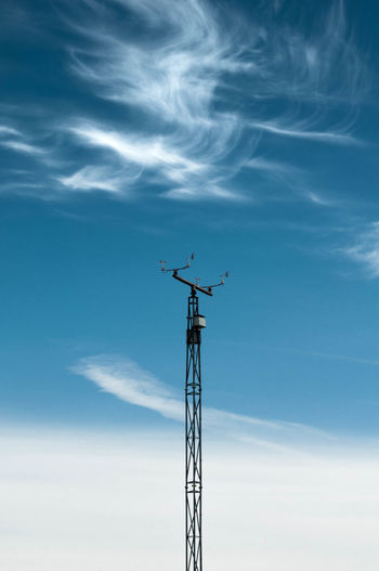 Low angle view of weather station against sky