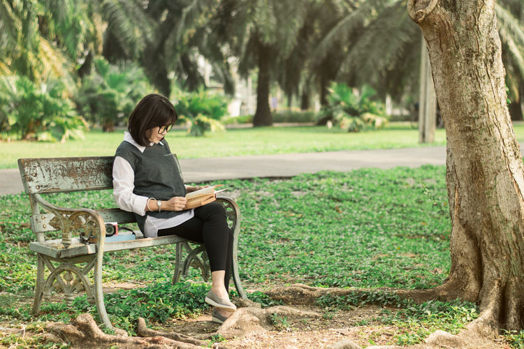 Woman reading book while sitting on bench at park