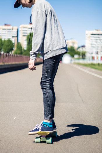 Girl Skateboarding On Road Against Sky