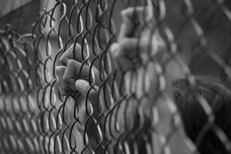 Close-Up Of Hands On Chainlink Fence